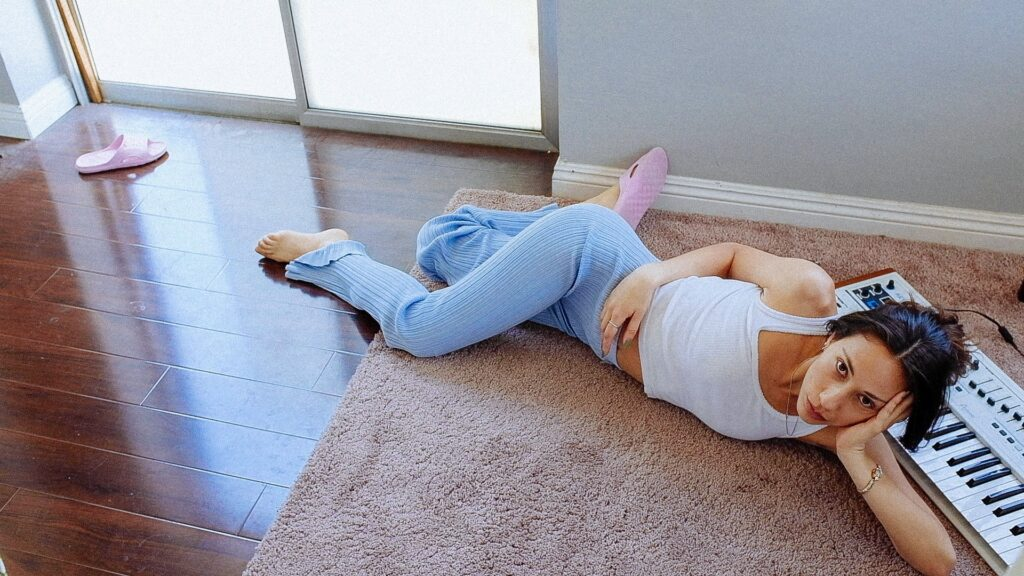 Singer Tei Shi lounges on the floor in front of a keyboard piano. She wears a white shirt and blue pants; pink slippers are left on the floor opposing Tei Shi.